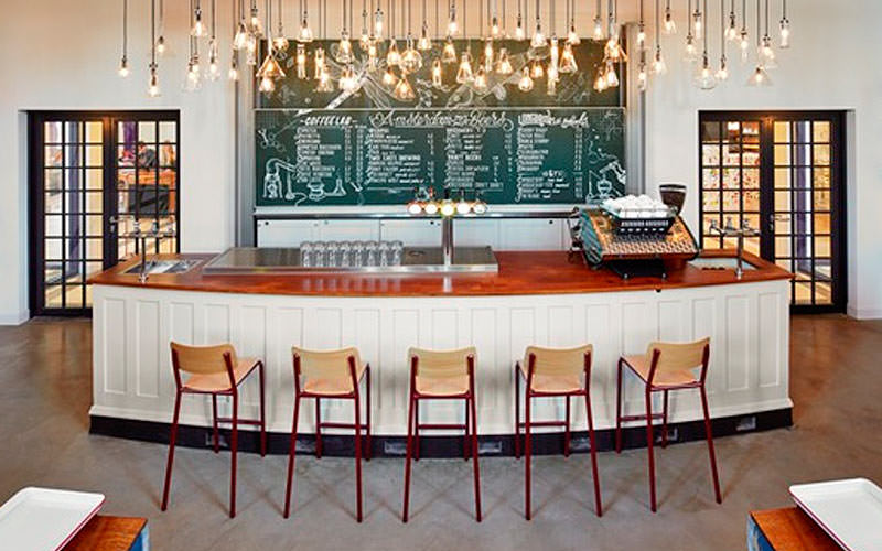 A white bar counter, with bar stools in front, with lights above and a green board in the background
