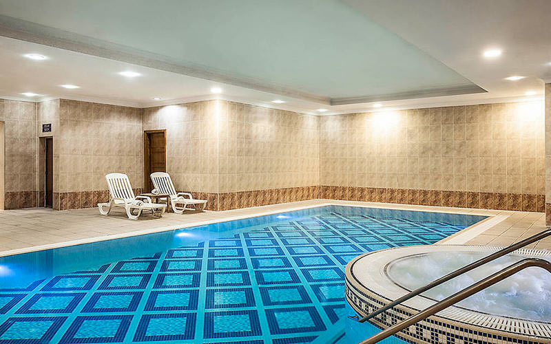 An indoor pool and Jacuzzi, with two sun loungers along the side