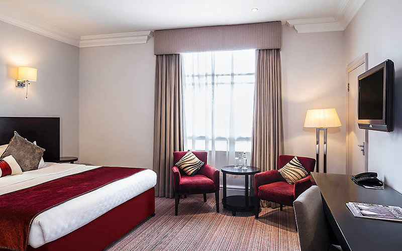 A double bed with a red throw in a hotel room, facing a black desk, TV and two red chairs