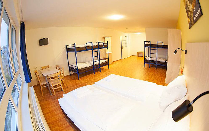 Two white single beds in the foreground, with tables and chairs and two blue bunk beds in the back