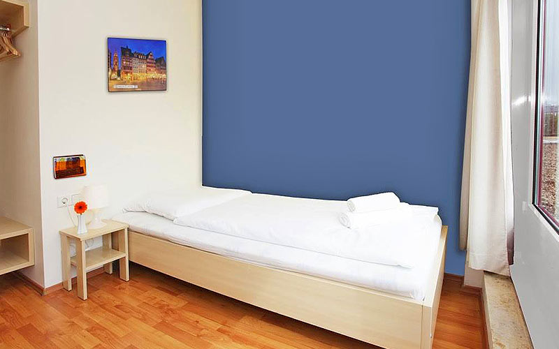 A white single bed in a blue hotel room, with a bedside table on the side