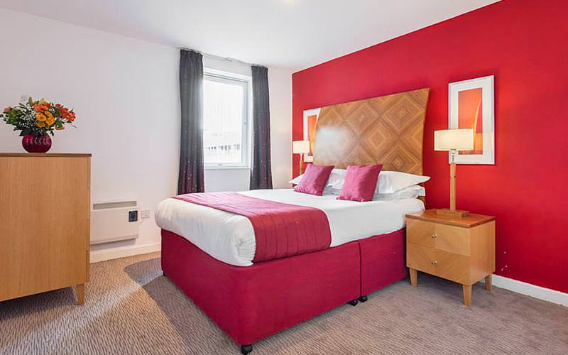 A double bed with red cushions and a throw on top, in a red hotel room