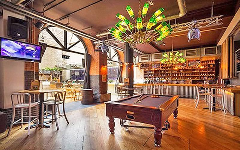 A indoor/outdoor bar area with a pool table and Jameson bottle chandelier