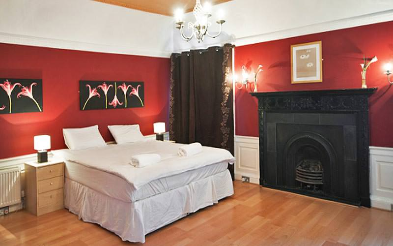 A spacious double bedroom with a black exposed fireplace and wooden floorboards
