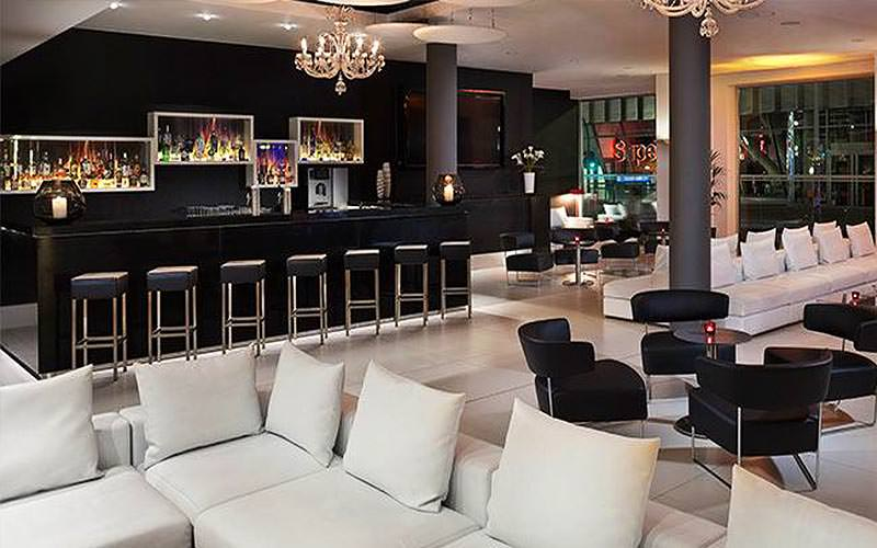 Black bar stools and white sofas in the foreground, with a black bar in the background