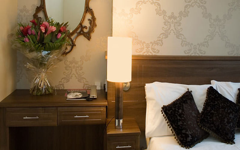 A bedside table, lamp and side of the bed in The New Steine Hotel