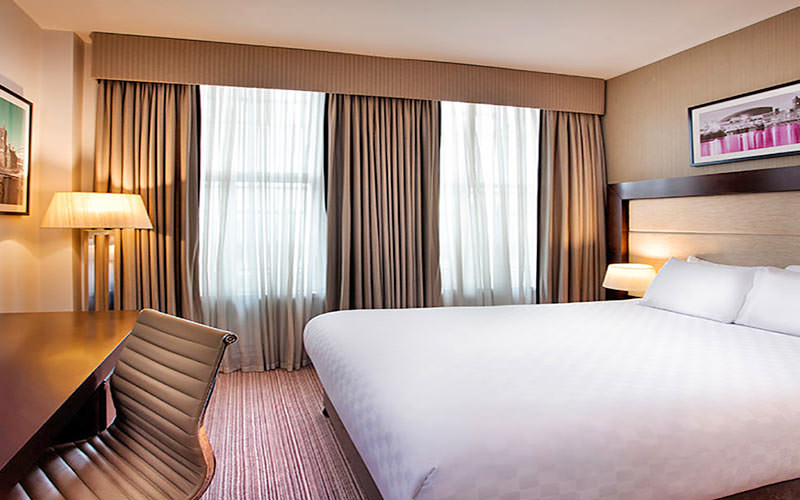 A spacious double room with ergonomic seat in the foreground and matching cream curtains at the double window