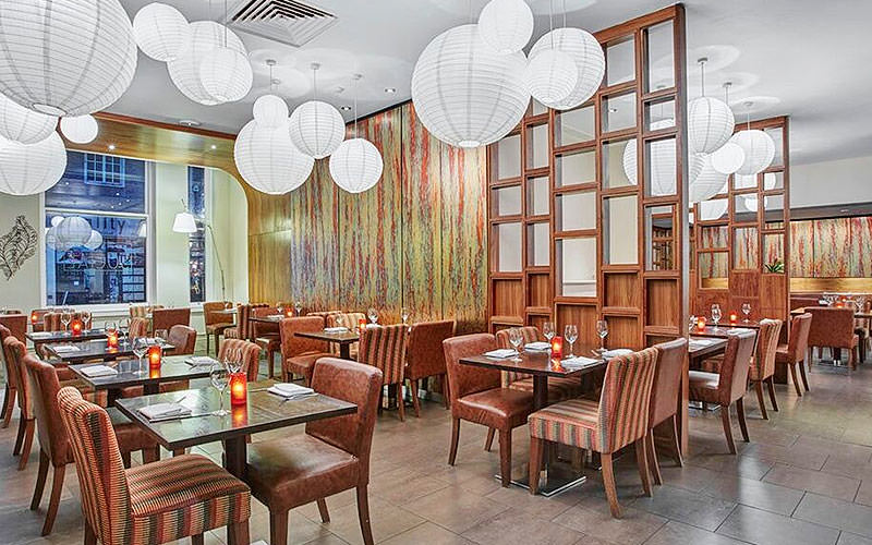 A restaurant set for dinner, with candles on the tables and paper lanterns for lampshades creating atmospheric lighting