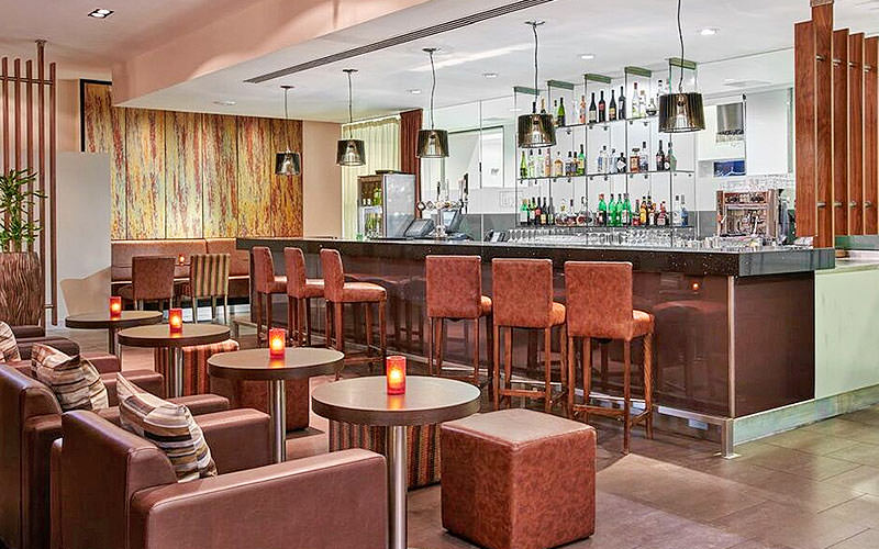 The bar area of Jurys Inn Cardiff, with seating and tables with candles on
