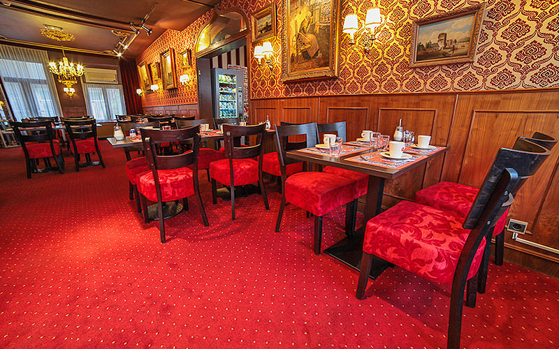 Tables and chairs in a red and grand-style hotel restaurant at Hotel de Paris, Amsterdam
