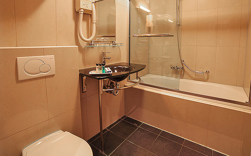 A bathroom featuring a bath, sink and toilet