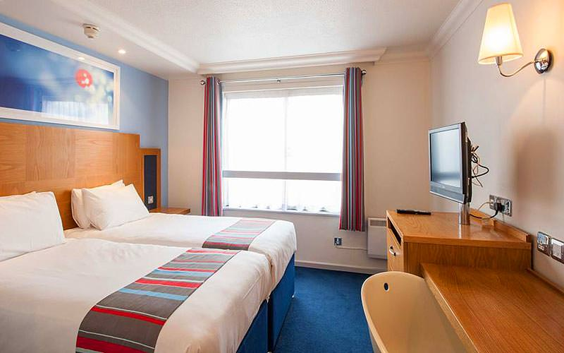 Two white double beds in a blue hotel room, facing two desk with a TV on top