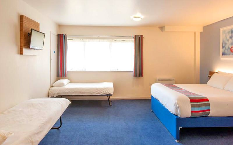 A double bed on the left side of a hotel room, facing two pull out beds