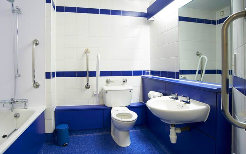 Blue and white tiled disabled bathroom, featuring a sink, toilet and bath