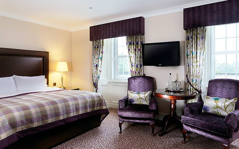 A double bed with checked bedding, with purple chairs, a table and TV on the wall in the foreground