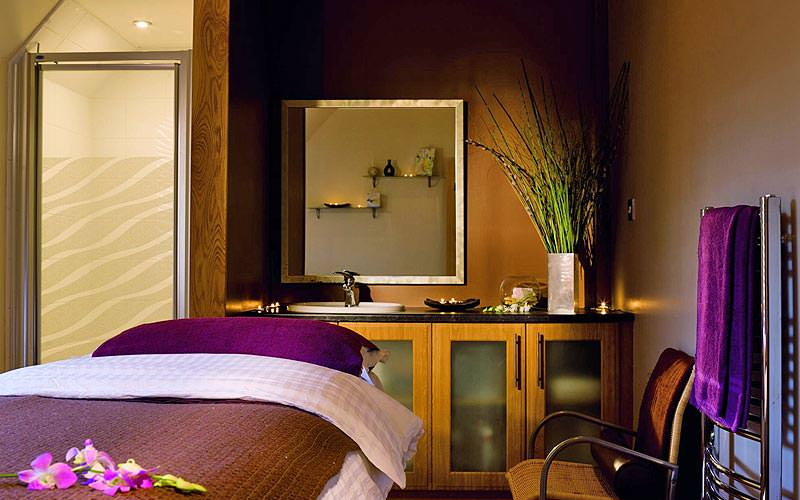 A treatment room with a massage bed and brown and purple decor
