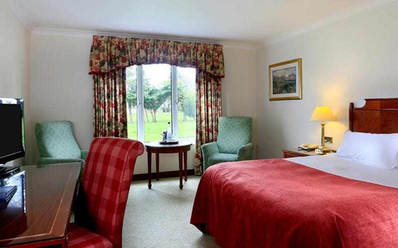 Image of a room with a double bed with a red bed throw with a big window looking out onto the green with floral curtains and a small round wooden table with two green chairs