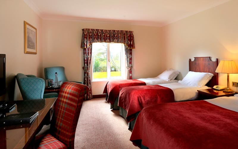 Image of a room with a double bed and two single beds with a window looking onto the green and wooden furniture
