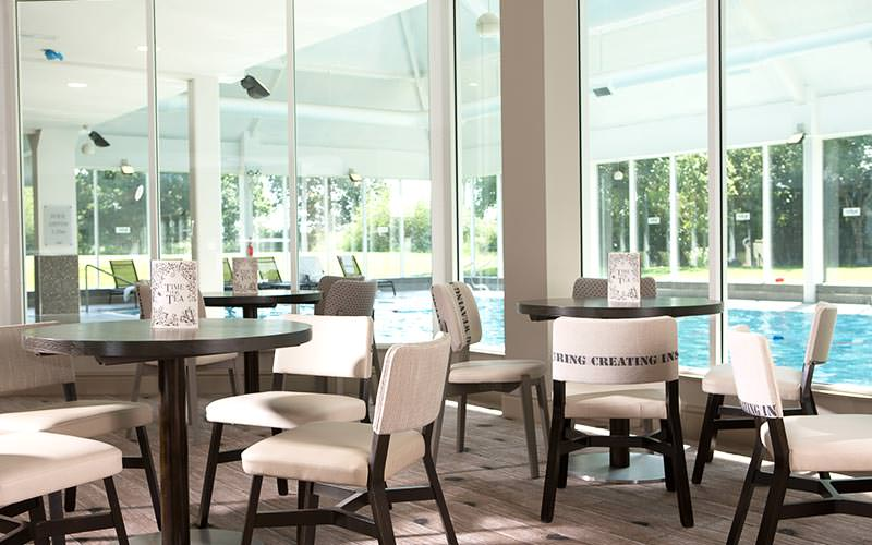 Tables and chairs in a room with glass walls, with an indoor pool in the background