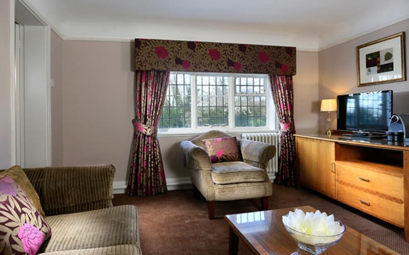 A room with a big window with floral curtains and a matching sofa and chair with cushions matching the curtains