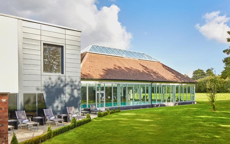 Image of the outside of the hotel with sun loungers and a massive extension with a swimming pool
