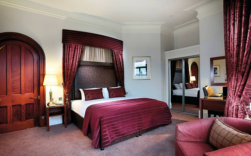 A traditional looking double bed with maroon curtains and bedding to match