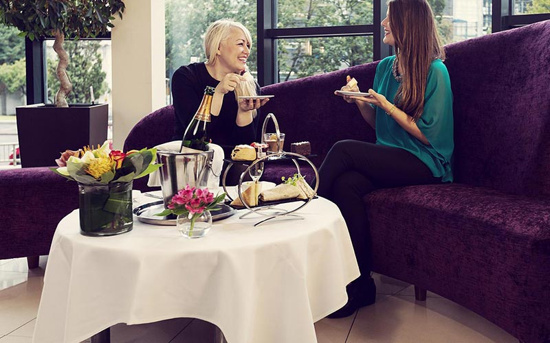 Two girls sitting on a purple sofa, enjoying afternoon tea