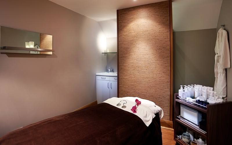 A beauty treatment room, with a massage bed in the middle and drawers topped with beauty accessories in the corner
