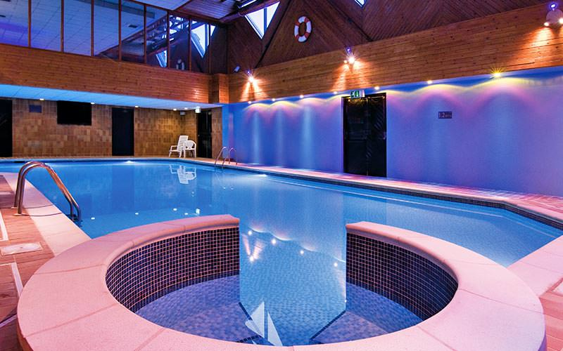 Indoor pool with an attached Jacuzzi in the foreground