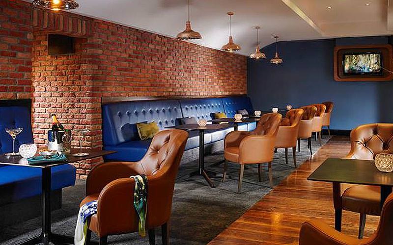 A bar and lounge area with exposed brickwork and long blue sofa benches