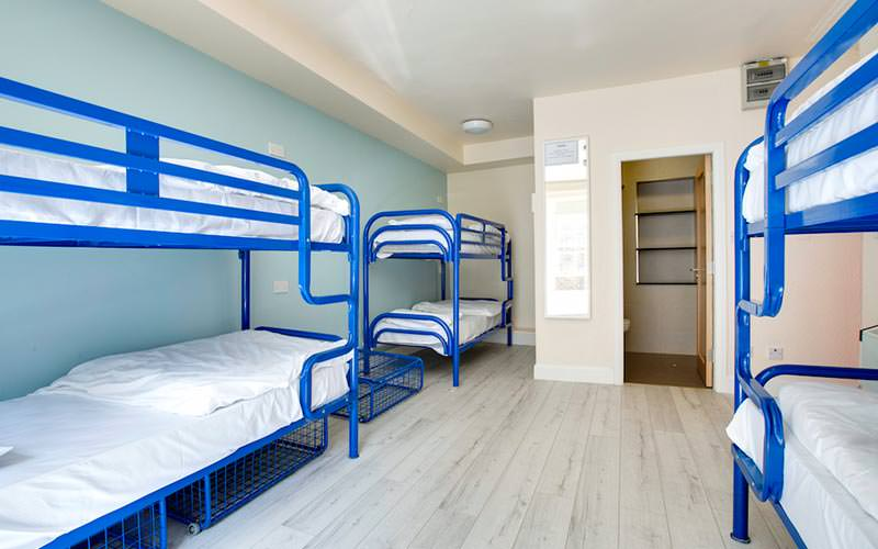 A wooden-floored room containing multiple blue metal framed bunk beds