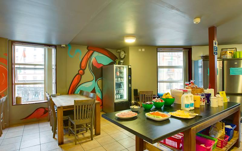 A communal kitchen and dining area with wall murals and a vending machine