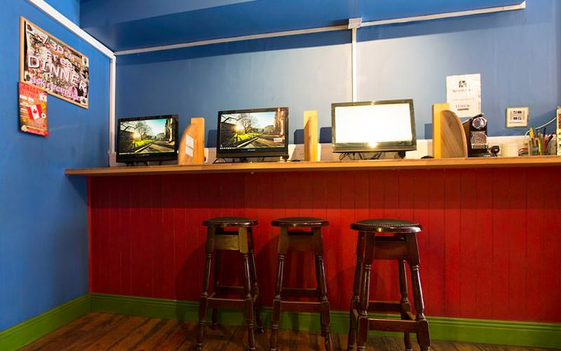Communal computers on a raised bench with bar stools