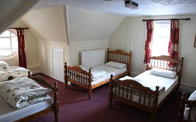 A large guest room with multiple single beds
