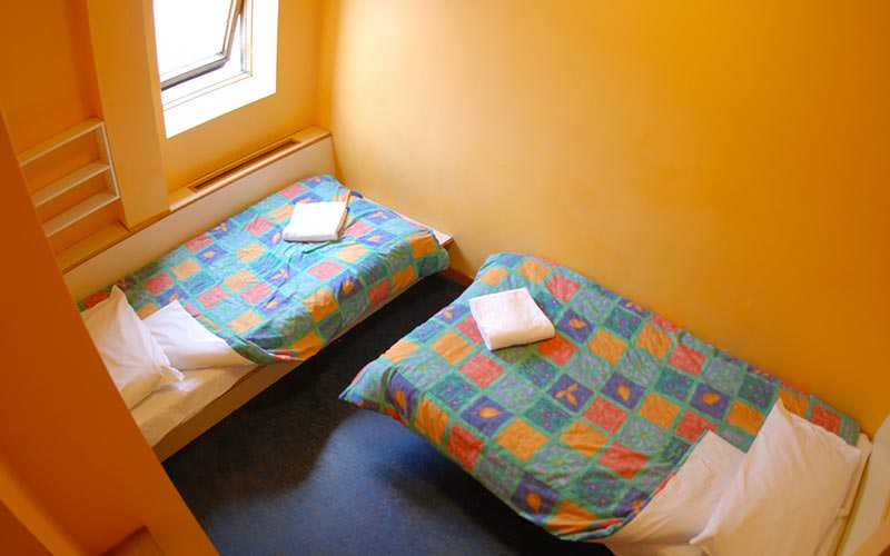 A bedroom with two twin beds and orange walls