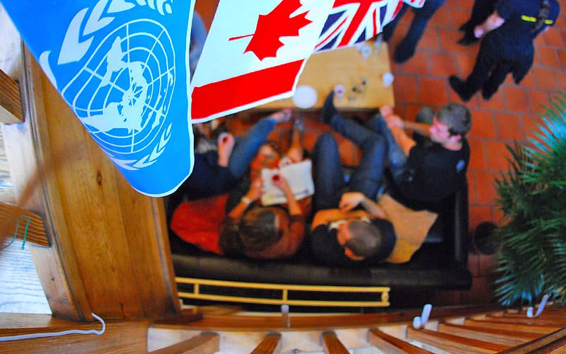 A top-down view of people sitting on a black sofa with flags visible at the top