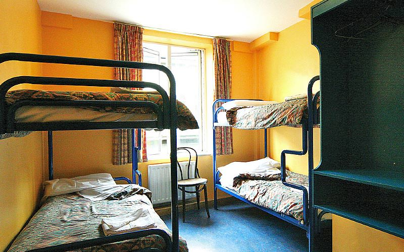 Wide bunk beds in a guest room with orange walls