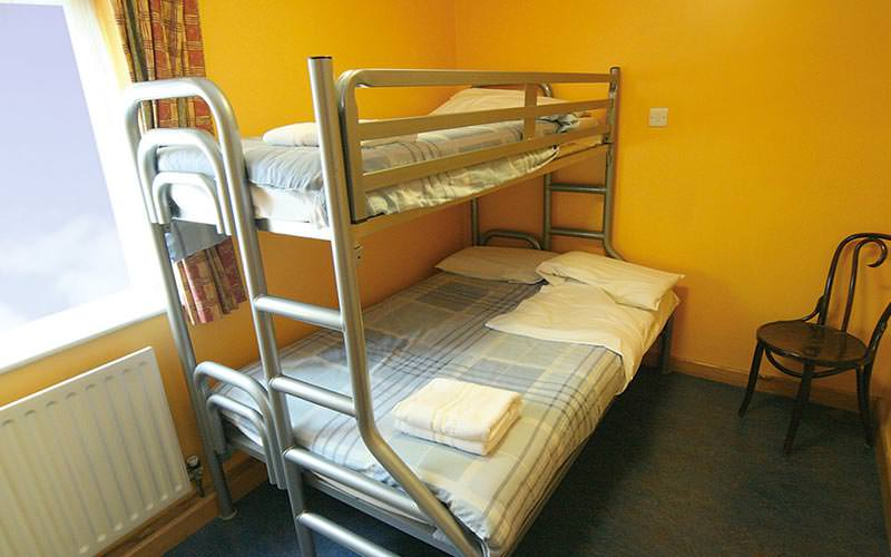 A metal framed bunk bed in a guest room with yellow walls