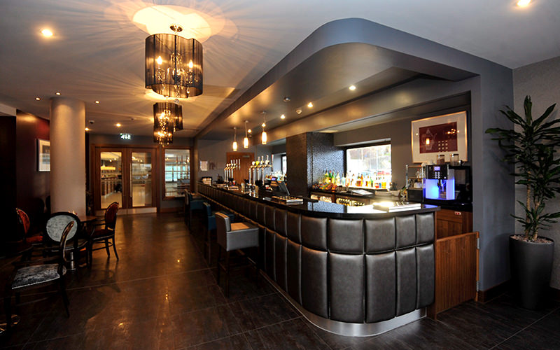 A hotel lobby bar with modern lighting and industrial style decor