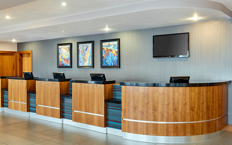 A hotel reception with wood panels and a tv