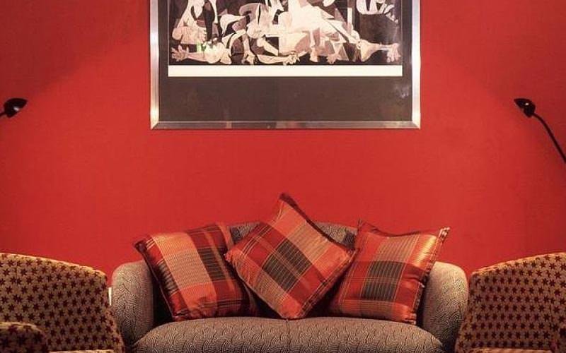 Three sofas in a room with red walls and a painting on the wall
