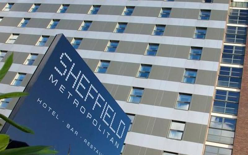 The Sheffield Metropolitan Hotel's exterior sign in the foreground, and hotel in the background