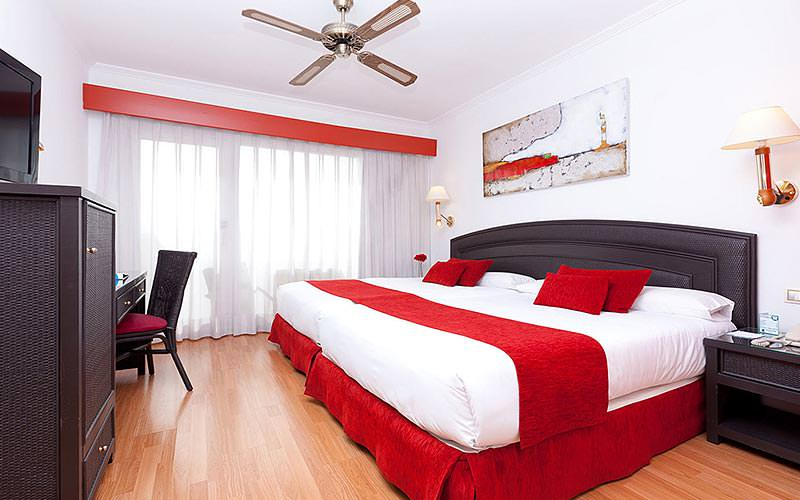 A spacious double room with white bedding and red runners and cushions, as well as a large ceiling fan