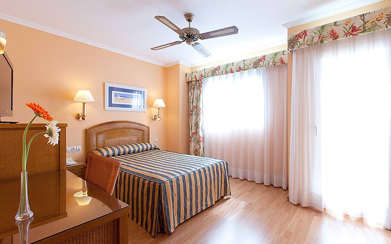 A double room with striped blue and yellow bedding, two windows with veils over and a large ceiling fan