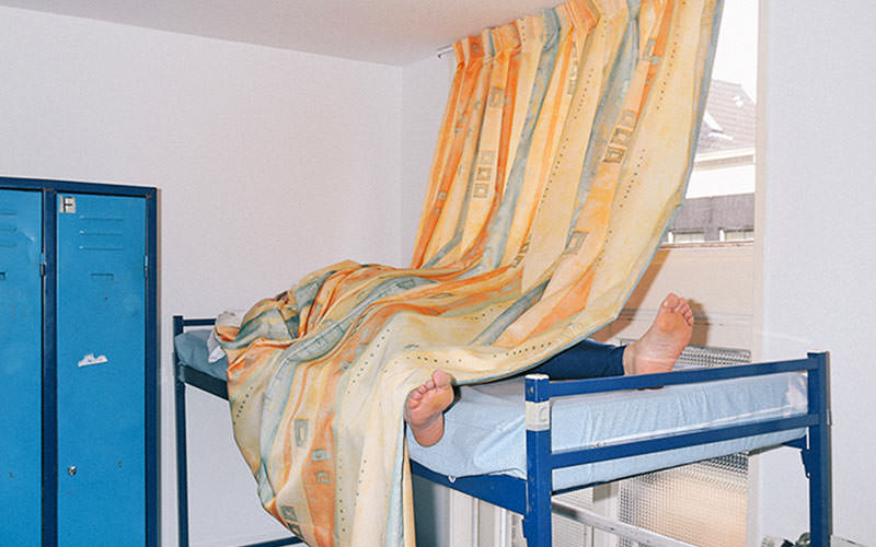 A curtain covering a man on the top of a bunk bed