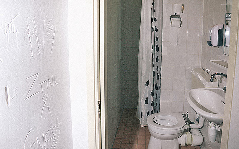 A white bathroom, featuring a sink and toilet in front of a white wall
