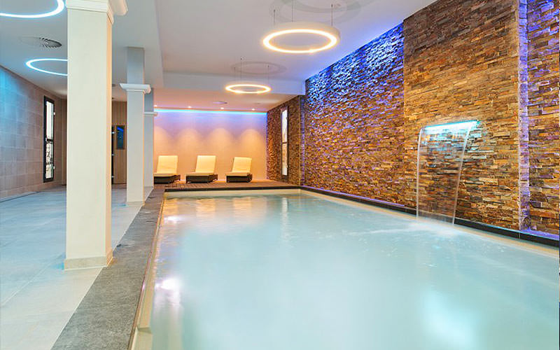 Indoor vitality pool, with water coming out of the exposed brick pool, and three sun loungers in the background