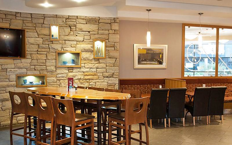 A dining area with an exposed brickwork wall, and lots of different seats