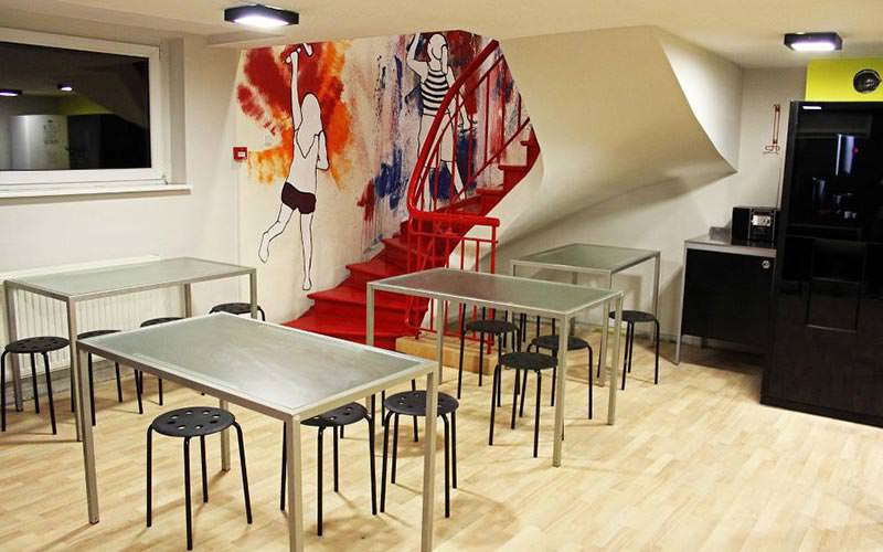 A dining area and red staircase at Corner Hostel