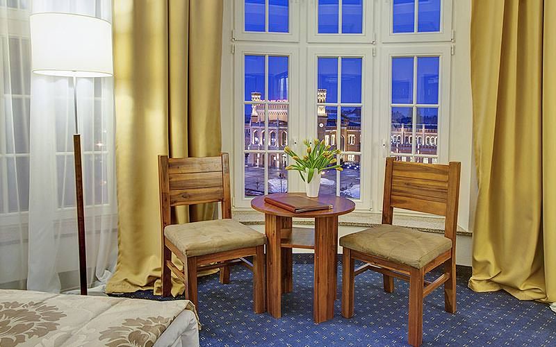 The seating area and window of a guest room in Hotel Piast